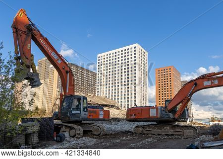 Concrete Remains Of Old Buildings And Excavators At A Construction Site. Housing Renovation. New Res