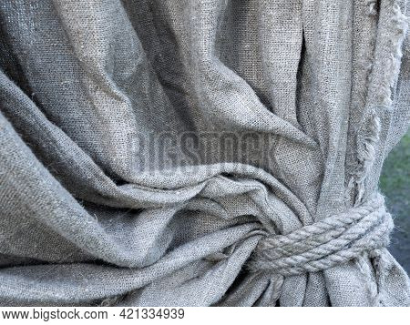 Detail Of Grey Textured Linen Curtain. Concept Of Drapery, Decoration By The Coarse Rustic Cloth