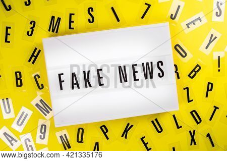 Lightbox With Message Fake News On Yellow Background With Black Letters Randomly Scattered. Concept