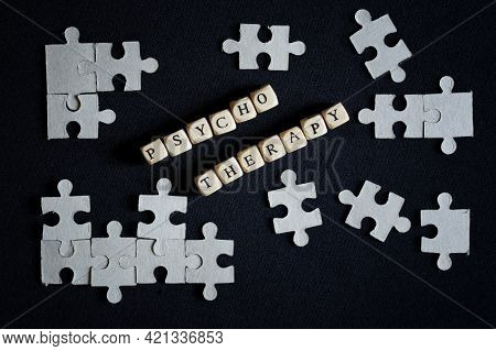 The Word Psychotherapy Made Up Of Letter Cubes Among Puzzles On A Dark Surface. The Concept Of Using