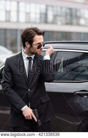 Bodyguard In Sunglasses With Security Earpiece Holding Gun And Talking Near Modern Auto.