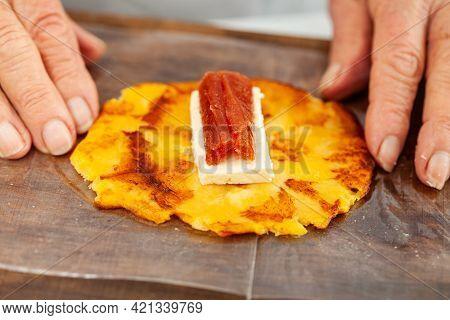 Senior Woman Preparing A Traditional Dish From El Valle Del Cauca In Colombia Called Aborrajado