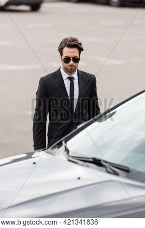 Bodyguard In Suit And Sunglasses With Security Earpiece Standing Near Modern Auto.