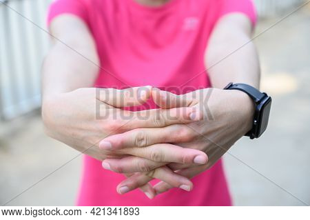 Close Up Of Woman Stretching Hands With Crossed Fingers Before Workout. Hand And Finger Exercises Ca