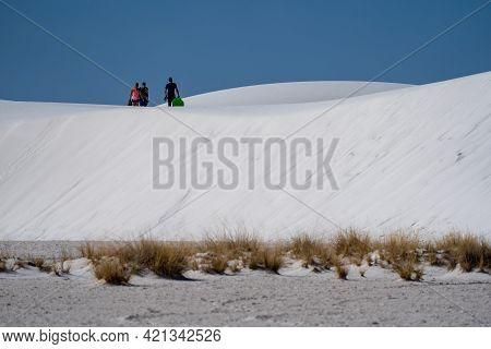 New Mexico, Usa - May 8, 2021: Tourists Hike With Sleds On The Gypsum Sand Dunes To Go Sledding In W