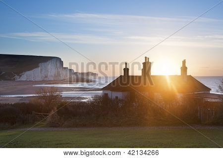Sunrise Over Coastguard Cottages At Seaford Head With Seven Sisters In Background