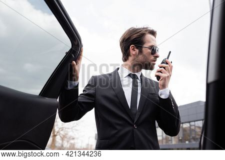 Side View Of Bodyguard In Suit And Sunglasses Using Walkie Talkie Near Modern Car.