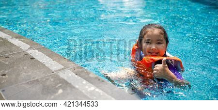 Asian Child Playing In The Pool. Wearing Orange Life Jacket, Smiling With Thumbs Up.