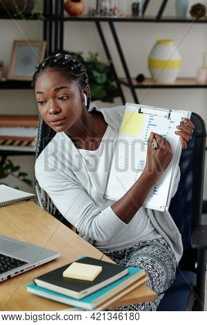 Young Bsuinesswoman Showing Report With Bar Chart When Having Online Meeting With Colleagues