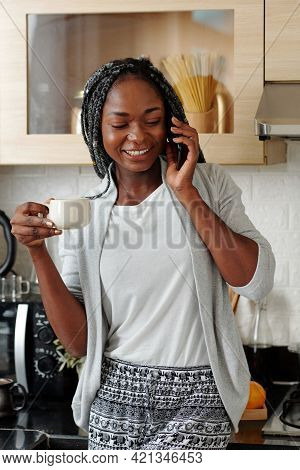 Pretty Young Woman In Loungewear Standing In Kitchen, Calling On Phone And Drinking Cup Of Morning C