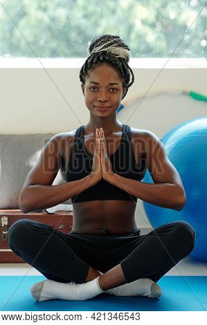 Smiling Beautiful Fit Young Woman Sitting In Lotus Position And Keeping Hands In Namaste Gesture