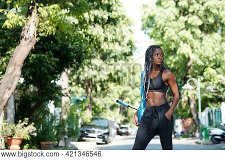Attractive Fit Young Woman With Braided Hair Standing On Road With Badminton Racquet In Hand