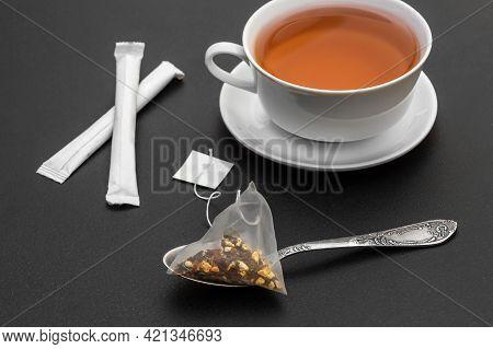 Cup Of Tea With Tea Spoon, Tea Bag And Sugar Packaging Sticks On Black.