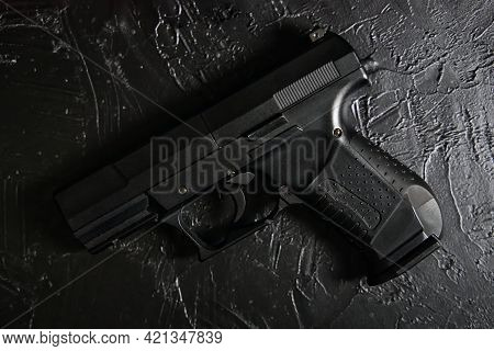 Gun On Black Texture Table. Firearm For Defense Or Attack. Ammunition Of Law Enforcement Agencies. P