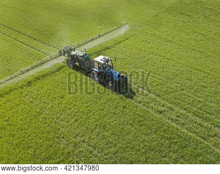 Aerial View Of Farming Tractor Spraying On Field With Sprayer, Herbicides And Pesticides At Sunset.