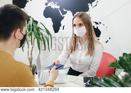 Travel Agent Having A Client In Face Mask In Modern Office Of Tour Agency, Giving Passport After Che