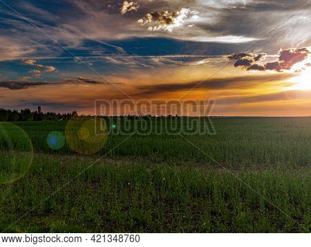 Clouds In The Orange Rays Of The Sunset Over A Green Farm Field. Sunny Sunset. Blue Sky With Clouds.
