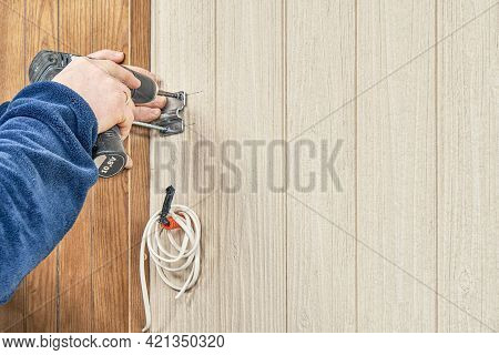 Craftsman In Blue Jacket Fastens Metal Attachment Plate For Lamp On Wooden Wall With Electrical Scre