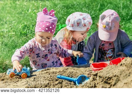 Omsk, Russia - June 21, 2019. Adorable Little Girls In Bright Clothes Play On The Playground With To