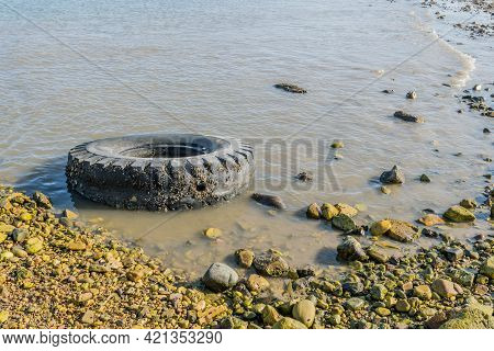 Old Tire Laying In Water Near Rocky Shore In Cove.
