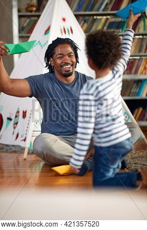 Young father playing with his son in a cheerful atmosphere at home. Family, together, love, playtime