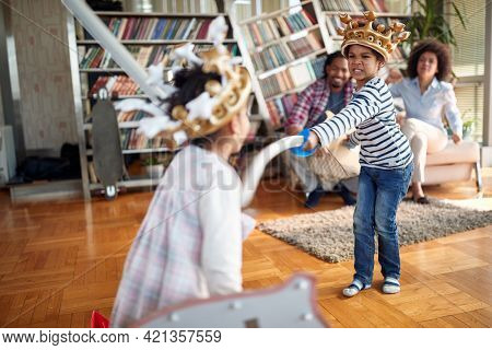 Kids are excited playing with swords while parents cheer in a playful atmosphere at home. Family, together, love, playtime