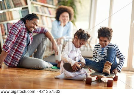 A young cheerful family having a good time in a relaxed atmosphere at home together. Family, together, love, playtime