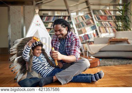 A little boy enjoys while with his father making soap bubbles in a relaxed atmosphere at home. Family, together, love, playtime