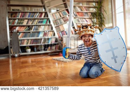 A cute little boy is yelling while playing on the floor in a playful atmosphere at home. Family, together, love, playtime