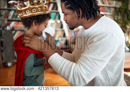 A young father helps his son blow his nose while playing in relaxed atmosphere at home together. Family, together, love, playtime
