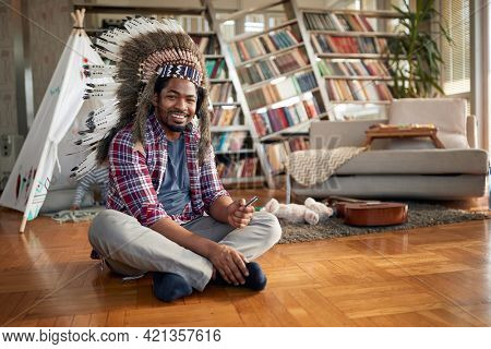 A young man with an indian headdress sitting on the floor in a relaxed atmosphere at home. Family, together, love, playtime