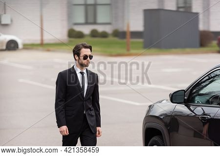 Bearded Bodyguard In Suit And Sunglasses With Security Earpiece Walking Near Modern Auto.