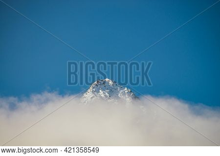 Wonderful View Of Sharp Snow-capped Mountain Top Above Thick Clouds In Sunshine. Bright Mountain Lan