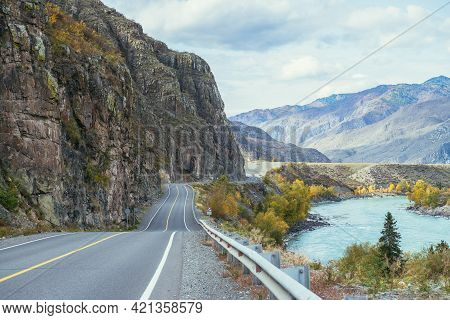 Vivid Autumn Landscape With Mountain Highway Along Big Mountain River In Sunshine. Bright Alpine Sce