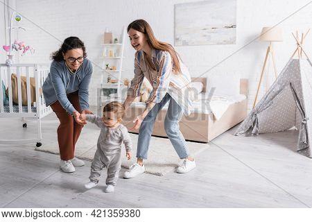 Happy Interracial Women Supporting Baby Boy Walking In Bedroom.