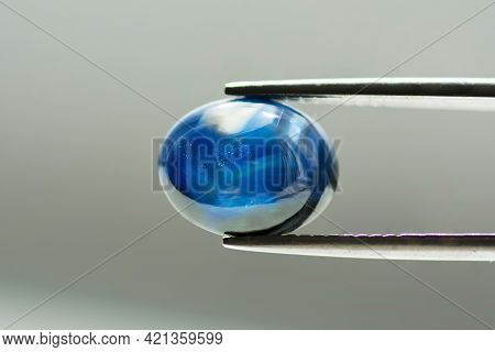 Natural Heated Blue Oval Cabochon Sapphire In Tweezers. Crystal Growth Color Pattern In Stone Massif