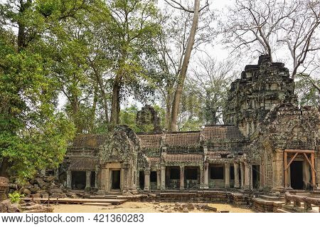 The Ancient Temple Of Angkor Is Dilapidated. Colonnades, Empty Doorways Are Visible. Carvings And Or