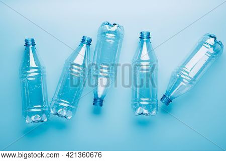 Empty Plastic Bottles On A Blue Background. Recycling Recyclable Plastic. Environment Protection