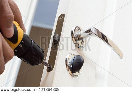 Worker Installing Or Repairing New Lock And Door Knob With Screwdriver. Locksmith Repair Or Install