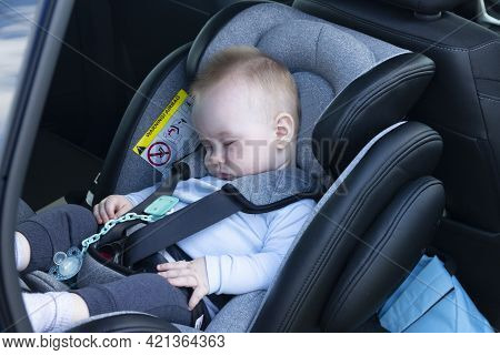 Sleeping Boy, An Baby, Six Months Old, Is Strapped Into A Car Seat In The Passenger Compartment.