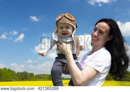 Baby Pilot, In A Pilot's Hat, Helmet, On The Hands Of A Young, Beautiful Brunette Girl. Copy Space.