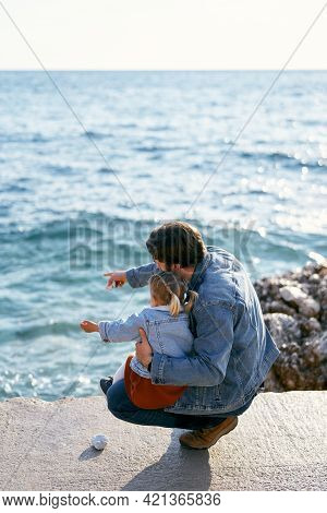 Dad Squatted Down Holding The Little Girl On His Lap On A Large Rock. Dad Points His Finger At The S