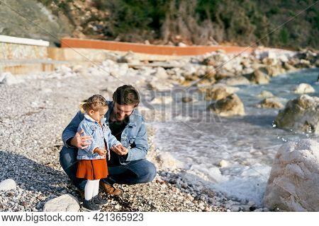 Smiling Dad Squatted Down Next To The Little Girl. She Gives Him Pebbles From A Rocky Beach By The W