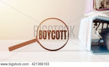 Magnifying Glass With The Word Boycott On Office Table.