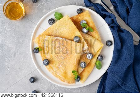 Homemade Crepes Served With Fresh Blueberries And Powdered Sugar On A White Plate On A Gray Concrete