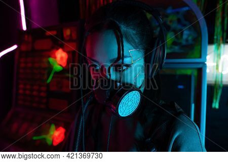 Young Asian Woman With Scar In Gas Mask And Wireless Headphones Looking Away.