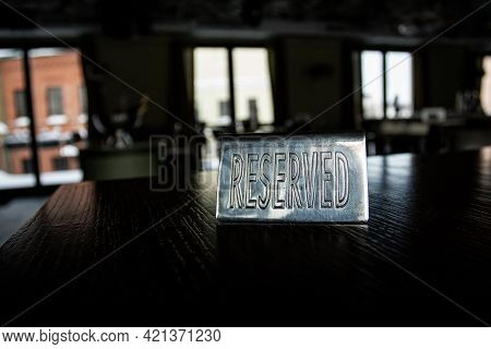 Metal Plaque Reserved On The Black Table In A Cafe Against A Background Of Blur And Light In The Win