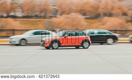 Red Mini Cooper Is Moving Fast Along A City Street. Moscow , Russia - April 2021