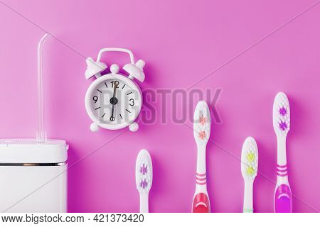 An Irrigator For Brushing Teeth On A Pink Background With A Clock And Toothbrushes.