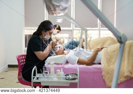 Professionals Working With A Clients In Beaty Salon. Woman Lying On Cosmetologiacal Coach During Las